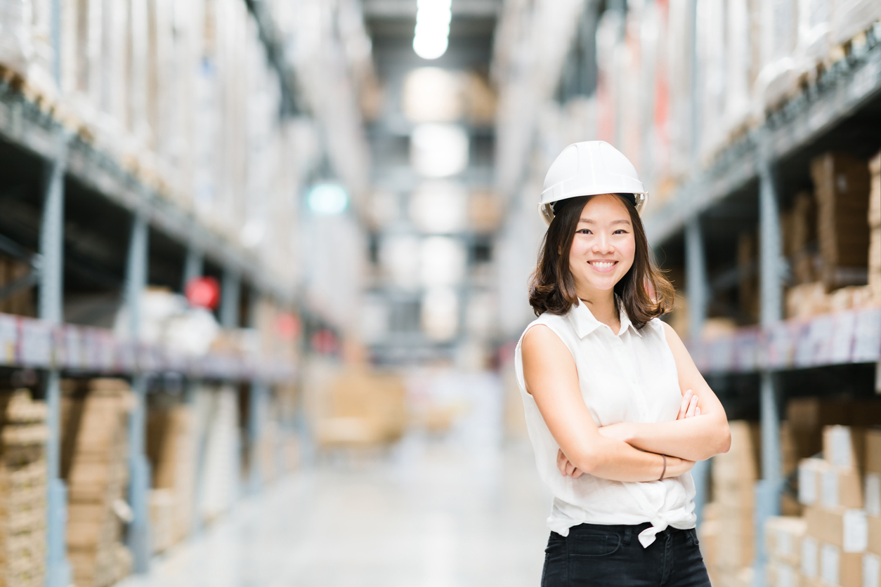 Young Asian engineer or technician smiling, warehouse blur background